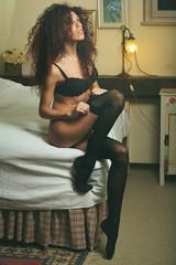 Sensual lingerie model dressing on bed