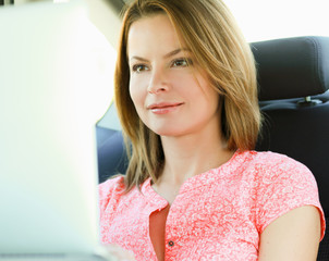 business travel: busy businesswoman with laptop in car.