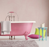 Classic pink bathtub with a stool and aged wood floor