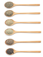 Various kind of spices on wooden spoon against white background