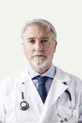Portrait of a senior doctor against white background