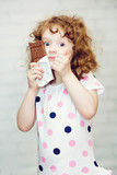 Girl with big blue eyes greedily holding chocolate, vertical ima