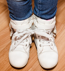Pair of white leather shoes with laces tied together on girl's l