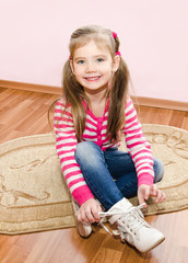 Cute little girl tying her white shoes at home