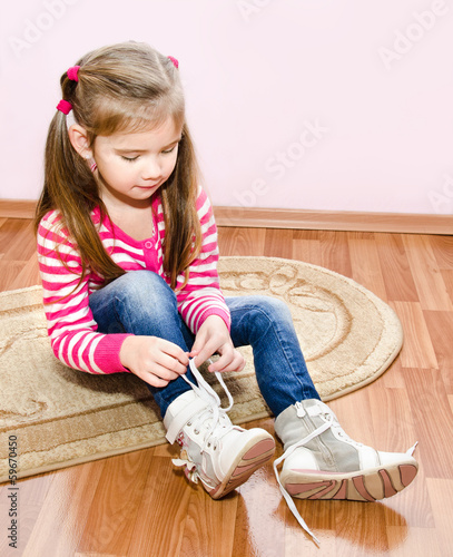 Cute little girl tying her white shoes