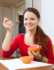 Happy beautiful woman in red eats grapefruit