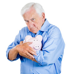 Old, retired man holding piggy bank. Financial decisions