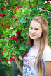 Teen girl near the red viburnum
