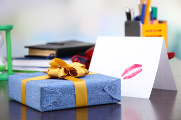Gift with card for loved one on desktop on room background