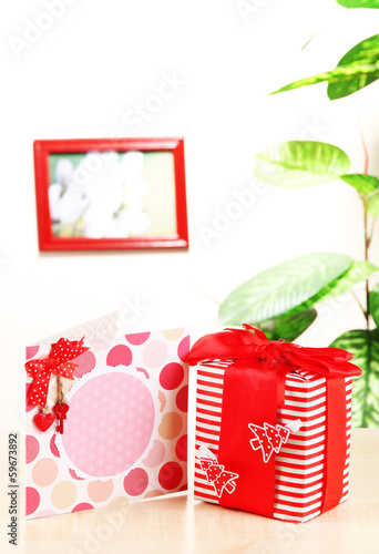 Gift with card on table on room background