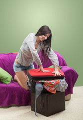 Girl trying to close her stuffed suitcase, green background