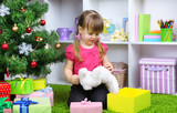 Little girl sitting near Christmas tree in room