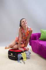 Girl trying to close her stuffed suitcase, gray background