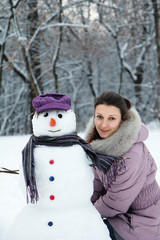 Beautiful brunette near a snowman
