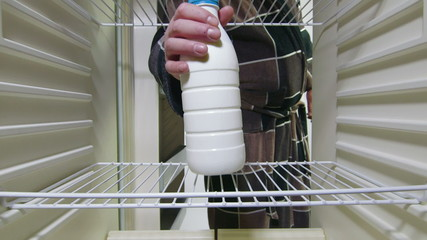Man takes out milk bottle from the refrigerator