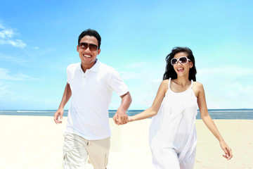 Beach couple in white dress running having fun laughing together