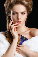 Beautiful girl in a coat and a blue dress. Evening make-up and h