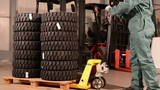worker with pallet truck move a pallet with forklift tires