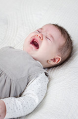 Baby girl crying over white bedcover