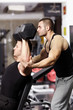 Personal trainer helping athletic man