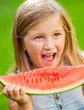 Adorable blonde girl eating watermelon outdoors