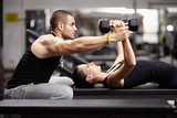 Fototapety Personal trainer helping woman at gym