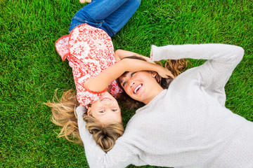 Mother and daughter lying together outside on grass