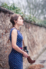 Beautiful young woman taking pictures with a vintage camera