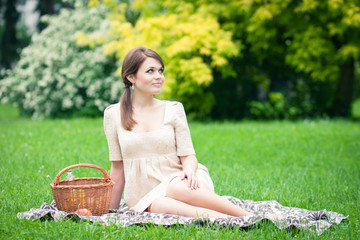 Beautiful elegant young woman picnicing in the park