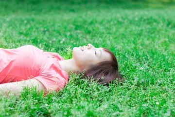 芝生の上で寝る女性