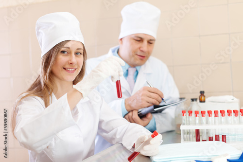Positive nurse and male doctor works with test tubes