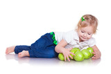 Adorable little girl sitting with green apples