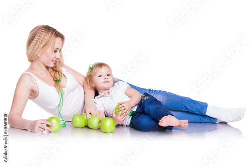 portrait of young mother and little daughter with apples
