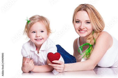 portrait of young mother and little daughter holding heart