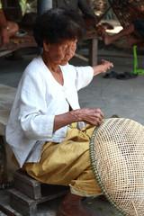 Thai Old woman weaving bamboo baskets