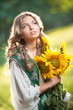 Young girl wearing Romanian traditional blouse holding sunflower