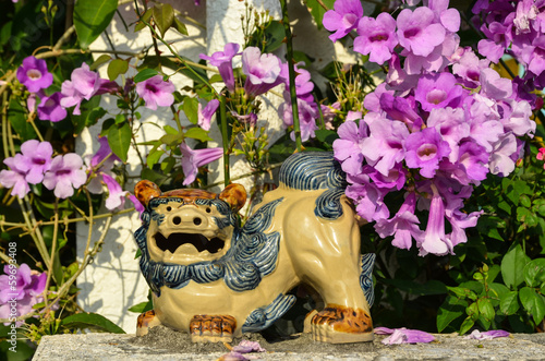 Shisa figure and pink flowers