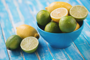 Ripe limes and lemons over blue wooden background