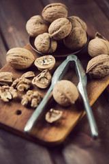 Walnuts and nutcracker, vintage wooden background, vertical shot
