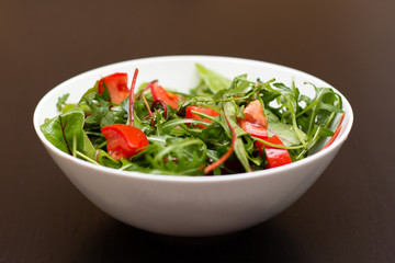 Light salad with tomatoes in white china bowl