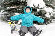 Boy with skis around snowy spruce