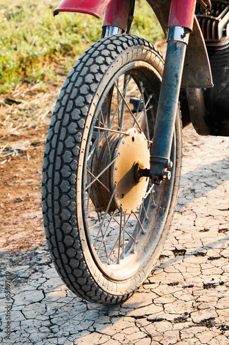 Old wheel motorcycle on a dirt road.