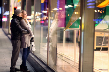 young lovers kissing on the street at night in the city, the str