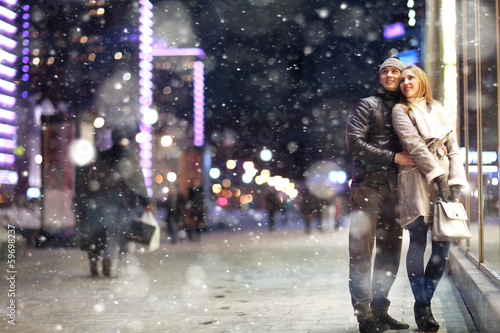 Leinwandbild Motiv Love man and woman embracing outdoors winter snowfall