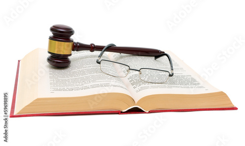 book of laws, glasses and gavel on white background close up