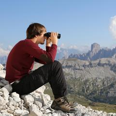 Junger Mann schaut in Bergen durch Fernglas