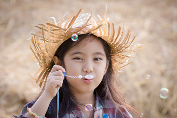 Happy Asian child playing bubble with straw stack