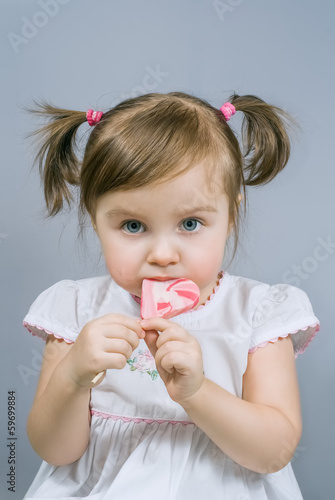 Little happy girl with big heart shaped swirl lollipop