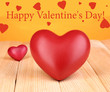 Decorative red hearts on wooden table on orange background