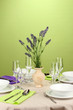 Table setting in violet and green tones on color  background